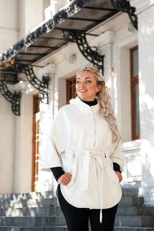 mujer elegante: joven rubia mujer llevaba blanco cálido abrigo de pie en la calle de la ciudad en otoño. Manera de la caída casual, elegante mirada cotidiana. Modelo más tamaño. Foto de archivo