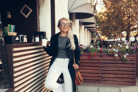 블랙 미디 코트, 흰색 바지, 유행을 좇는 안경 마시는를 입고 금발 여자는 도시 거리에 야외 카페에서 종이 컵에 커피를 빼앗아. 캐주얼 패션, 우아한