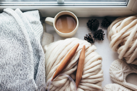 Stack of cozy knitted sweaters, thick yarn and wooden needles on window sill, top view. Chunky knit. Morning coffee in lazy winter weekend.