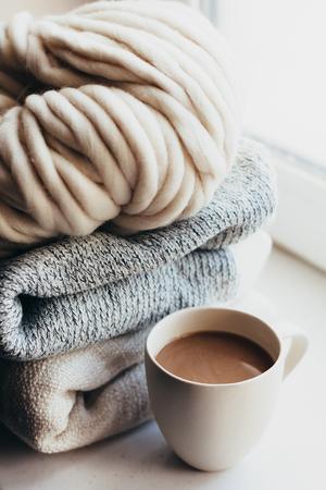 tejido de lana: Pila de suéteres de punto acogedoras y de hilos gruesos en alféizar de la ventana. de punto grueso. café de la mañana en invierno fin de semana perezoso. Foto de archivo