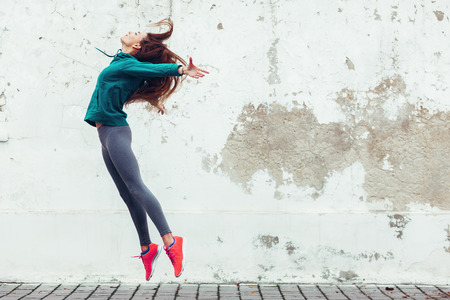 Fitness sport girl in fashion sportswear dancing hip hop in the street, outdoor sports, urban style Stockfoto