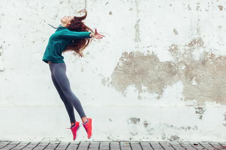 moda: Menina do esporte da aptidão no sportswear moda hip hop dança na rua, desportos ao ar livre, estilo urbano