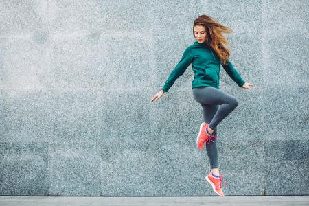 Fitness sportovn� d�vka v m�dn� sportovn� oble?en� d?l� j�gu fitness cvi?en� na ulici, pl�ov� sporty, m?stsk� styl