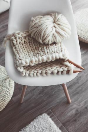 knit: Thick yarn and wooden needles on modern plastic chair in living room, top view. Chunky knit. Details of white scandinavian interior.