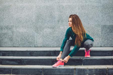 Fitness sport meisje in de mode sportkleding doen yoga fitness oefening in de straat, buiten sporten, stedelijke stijl