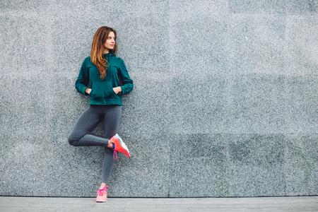 Menina do esporte da aptidão no sportswear forma fazendo exercícios de fitness yoga na rua, desportos ao ar livre, estilo urbano