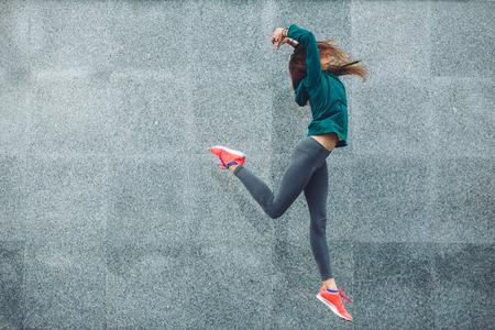 Muchacha del deporte de la aptitud en ropa deportiva de moda bailando hip hop en la calle, deportes al aire libre, estilo urbano Foto de archivo - 66891224