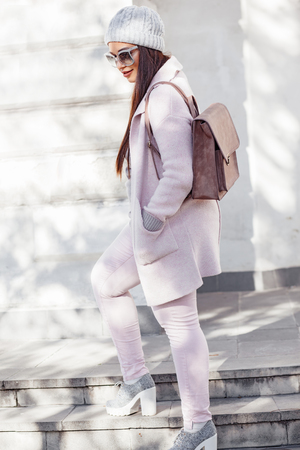 cold season: Young stylish woman wearing pink warm coat, pants and handbag walking in the city street in cold season. Winter fashion, elegant look, outfit in pastel colors. Plus size model. Stock Photo