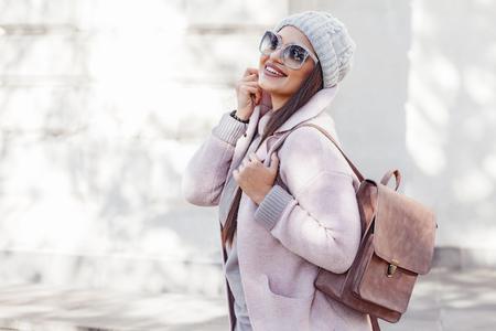 若いスタイリッシュな女性が身に着けているピンクの暖かいコート、パンツ、寒い季節での街を歩いてのハンドバッグ。冬のファッション、エレガ