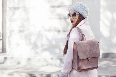 Jonge modieuze vrouw, gekleed in roze warme jas, broek en handtas wandelen in de stad straat in koude seizoen. Winter mode, elegante look, outfit in pastel kleuren. Plus size model.