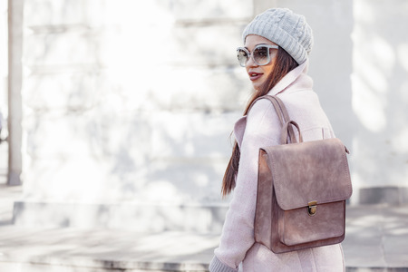 Young stylish woman wearing pink warm coat, pants and handbag walking in the city street in cold season. Winter fashion, elegant look, outfit in pastel colors. Plus size model. Stock Photo