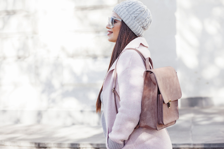 pastel shades: Young stylish woman wearing pink warm coat, pants and handbag walking in the city street in cold season. Winter fashion, elegant look, outfit in pastel colors. Plus size model. Stock Photo