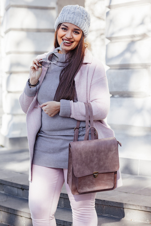 Young stylish woman wearing pink warm coat, pants and handbag walking in the city street in cold season. Winter fashion, elegant look, outfit in pastel colors. Plus size model. Banco de Imagens
