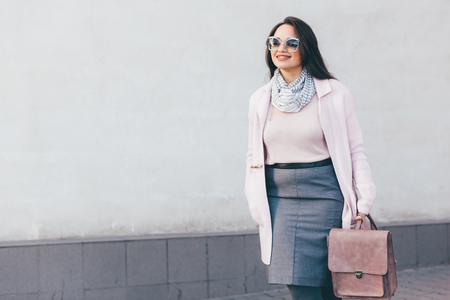 cold season: Young stylish woman wearing pink warm coat, skirt and handbag walking in the city street in cold season. Winter fashion, elegant look, outfit in pastel colors. Plus size model.