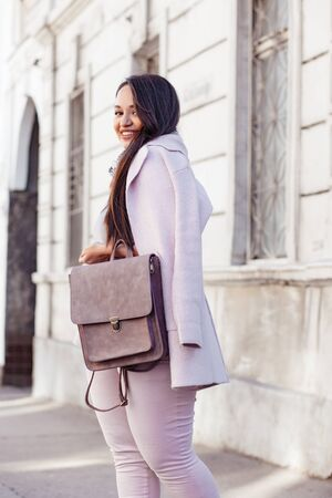 chubby girl: Young stylish woman wearing pink warm coat, pants and handbag walking in the city street in cold season. Winter fashion, elegant look, outfit in pastel colors. Plus size model. Stock Photo
