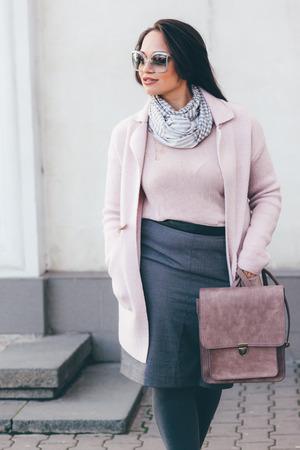Młoda kobieta ma na sobie różowy stylowy ciepłym Herb, spódnicę i torebkę przechadzającego się po ulicy miasta w zimnej porze roku. Zima mody, elegancki wygląd, strój w kolorach pastelowych. Plus size model. Zdjęcie Seryjne