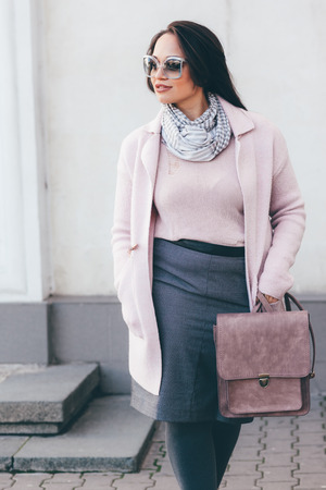winter fashion: Young stylish woman wearing pink warm coat, skirt and handbag walking in the city street in cold season. Winter fashion, elegant look, outfit in pastel colors. Plus size model.