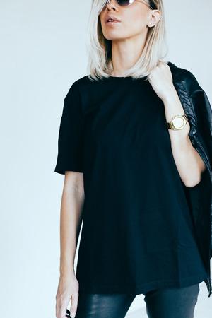 Mode-Modell in schwarzer Kleidung. Lederjacke und Hose, leere T-Shirt und eine Sonnenbrille. Straße im urbanen Stil.