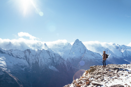 Man met rugzak wandelen in de bergen. Koud weer, sneeuw op de heuvels. Winterwandelingen.