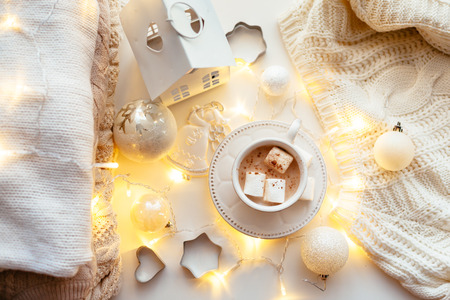 string top: White Christmas decor: warm sweater, cup of hot cocoa with marshmallow and led string lights. Winter mood, holiday decoration, top view point. Stock Photo