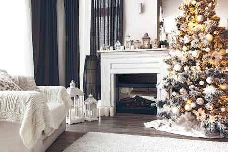 담요와 크리스마스 트리, 벽난로와 안락의 아름다운 휴가 장식 된 객실입니다. 아늑한 겨울 장면. 조명 화이트 인테리어.