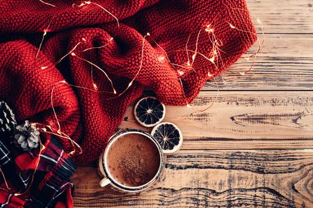 Winter gemütliche Szene. Warme Strickdecke und Tasse heißen Kakao, LED-Leuchten String. Weihnachtsferien Dekor.