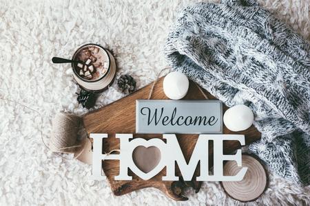 Winter huiselijke scène, scandinavische stijl. Warme gebreide trui, kaarsen, kopje zoete chocolademelk met marshmallows en andere decor op dienblad in bed. Houten ambachtelijke brieven Welcome Home. Lui koud weekend.