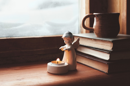 Warm und bequem Winter-Konzept. Buch, Tasse Tee und Kerze auf hölzernen Fensterbrett im alten Haus. Das Lesen und in kalten verschneiten Wetter zu Hause entspannen. Quiet silent gemütliche Szene.