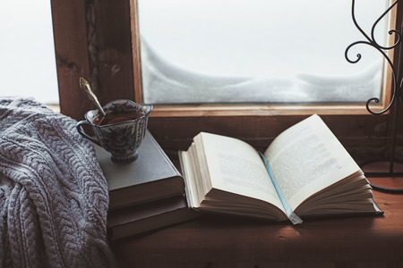 old windows: Warm and comfy winter concept. Book, cup of lemon tea and sweater on wooden window sill in old house. Reading and relaxing in cold snowy weather at home. Quiet silent homely scene.