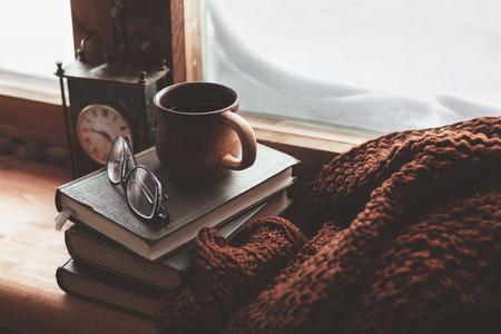 concept hiver chaud et confortable. Livre, tasse de thé et un pull sur bois rebord de la fenêtre dans la vieille maison. La lecture et de détente dans un temps neigeux froid à la maison. Calme scène chaleureuse silencieuse.