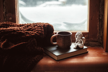 old windows: Warm and comfy winter concept. Book, cup of tea and candlestick on wooden window sill in old house. Reading and relaxing in cold snowy weather at home. Quiet silent homely scene.