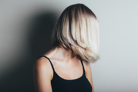 medium length: Model with unrecognizable face with blond shiny hair. Woman bob haircut styling. Stock Photo