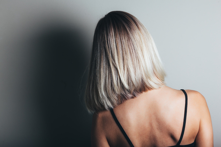 Model with unrecognizable face with blond shiny hair. Woman bob haircut styling. Back view