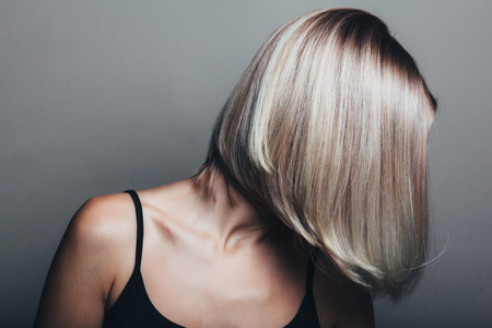 Model with unrecognizable face with blond shiny hair. Woman bob haircut styling. Stock Photo