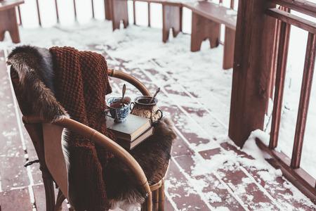 눈이 통나무 집의 현관 갑판에 모피 커버와 함께 자. 차, 따뜻한 담요와 독서. 추운 겨울 긴장된 주말 스톡 콘텐츠