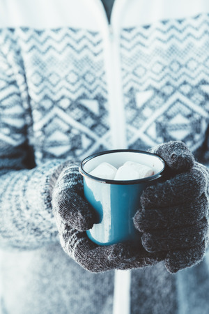 cold season: Closeup photo of tin mug with cocoa and marshmallows in male hands in mittens. Traveller in sweater drinking hot beverage in cold season. Snowy winter travel.