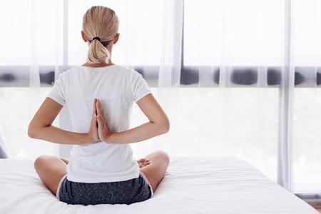 donna che fa esercitazione di yoga sul letto a casa. allenamento ... - Donne In Camera Da Letto