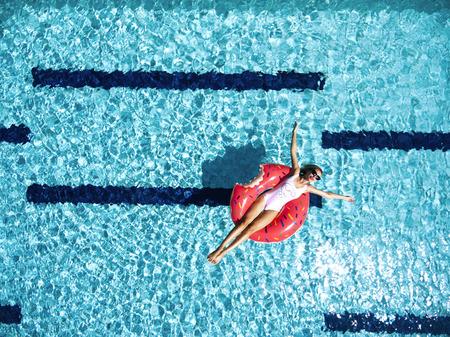 Femme de détente sur donut lilo dans l'eau de la piscine en journée chaude et ensoleillée. vacances idyllique d'été. Vue de dessus. Banque d'images - 69179293