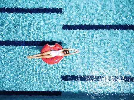 Mujer que se relaja en lilo rosquilla en el agua de la piscina en un día soleado caliente. vacaciones de verano idílico. Vista superior.