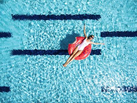 Vrouw ontspannen op donut luchtmatras in het zwembad water in warme zonnige dag. Zomervakantie idyllisch. Bovenaanzicht. Stockfoto