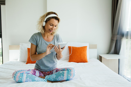 Youn woman in headphones is chilling and listening to music using tablet pc on bed in bedroom at home