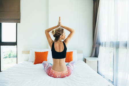 Woman doing yoga exercise on bed at home. Morning workout in bedroom. Healthy and sport lifestyle. Stockfoto