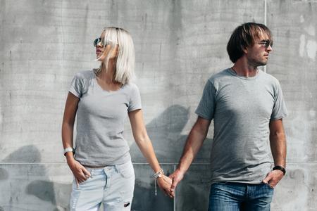 Dos modelos de última moda hombre y mujer que llevaba en blanco camiseta gris, pantalones vaqueros y gafas de sol posando contra la pared rugosa concreto en la calle de la ciudad, maqueta camiseta delante de pareja, estilo urbano