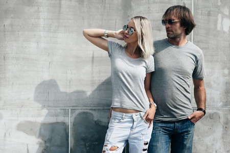 Two hipster models man and woman wearing blank gray t-shirt, jeans and sunglasses posing against rough concrete wall in the city street, front tshirt mockup for couple, urban style 版權商用圖片 - 69431100
