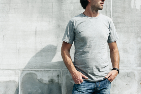 Man wearing blank t-shirt posing against gray concrete wall in the city street, front tshirt mockup on model, urban style