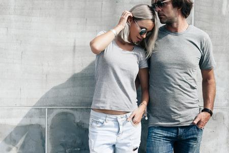 Dwa modele hipster mężczyzna i kobieta ma na sobie puste szare t-shirt, dżinsy i okulary stwarzających przeciwko szorstki betonowy mur na ulicy miasta, przedni tshirt makieta para, miejskiego stylu Zdjęcie Seryjne