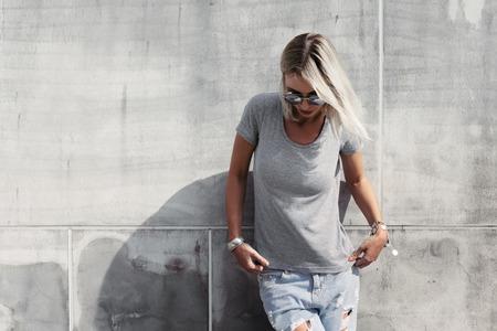 Hipster девушка носить пустые футболки, модные солнцезащитные очки и джинсы, создавая против грубого concgrete стены, минималистский стиль улица