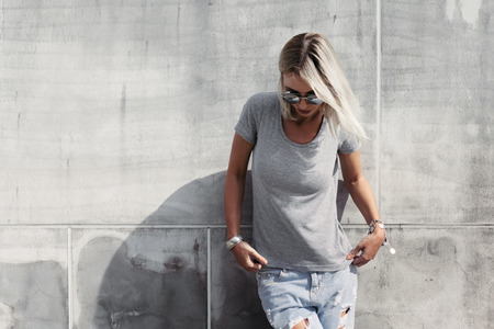 Hipster girl wearing blank t-shirt, fashion sunglasses and jeans posing against rough concgrete wall, minimalist street style