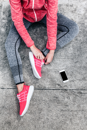 Fitness sport woman in fashion sportswear doing yoga fitness exercise in the city street over gray concrete background. Outdoor sports clothing and shoes, urban style. Tie sneakers, top view. Standard-Bild