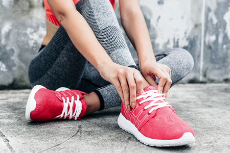 Fitness sport woman in fashion sportswear doing yoga fitness exercise in the city street over gray concrete background. Outdoor sports clothing and shoes, urban style. Tie sneakers.